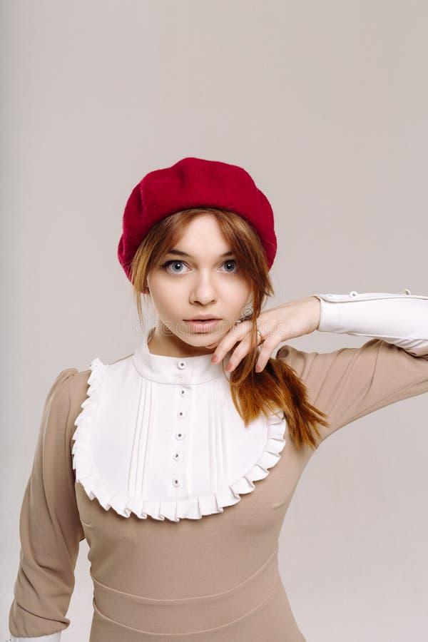 有大蓝眼睛的可爱的深色的女孩在红色贝雷帽和米黄礼服 免版税库存照片