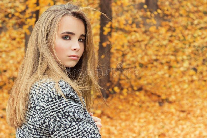 有大蓝眼睛的美丽的迷人的年轻可爱的女孩,与长的黑发在外套的秋天森林里 免版税库存图片