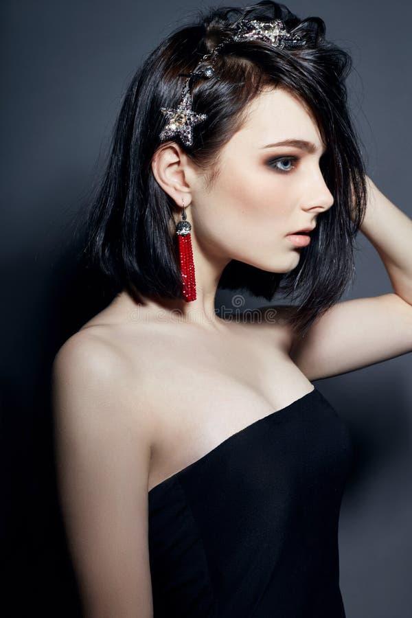 有大蓝眼睛耳环和项链首饰的美丽的深色的女孩 时尚画象自然构成完善的干净的皮肤 免版税库存照片