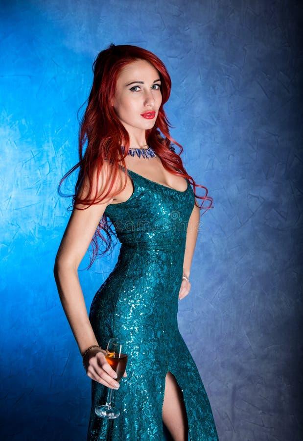 有大蠢材的典雅的性感的妇女在拿着葡萄酒杯用香槟的紧的蓝色礼服 免版税库存图片