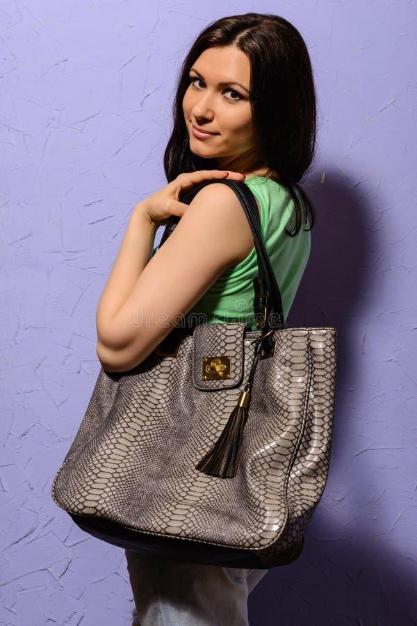 有大袋子的可爱的年轻深色的女孩蛇皮 免版税库存照片