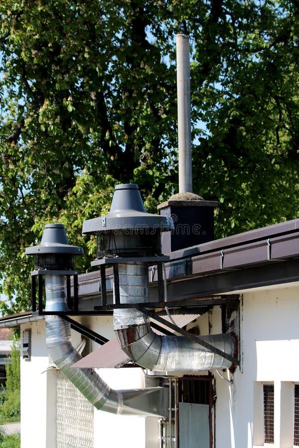 有大过滤器和在顶端金属保护的餐馆厨房工业烟囱在与高大的树木的大厦边缘登上了 库存照片