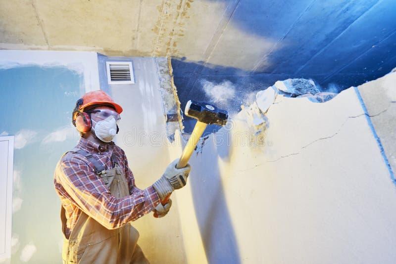 有大锤的工作者在室内墙壁毁坏 库存照片