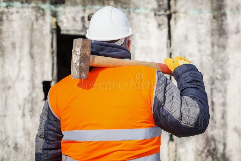 有大锤的工作者对墙壁 库存照片