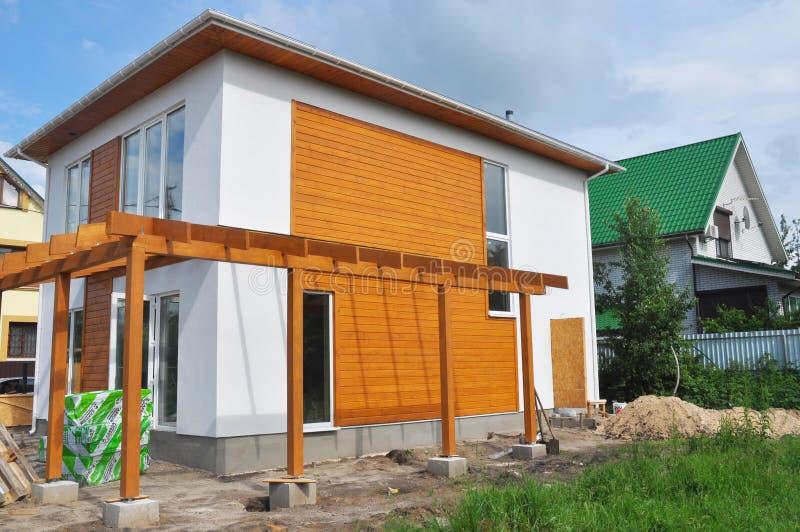 有大阳台露台和堆绝缘材料的未完成的现代房子建筑 库存照片