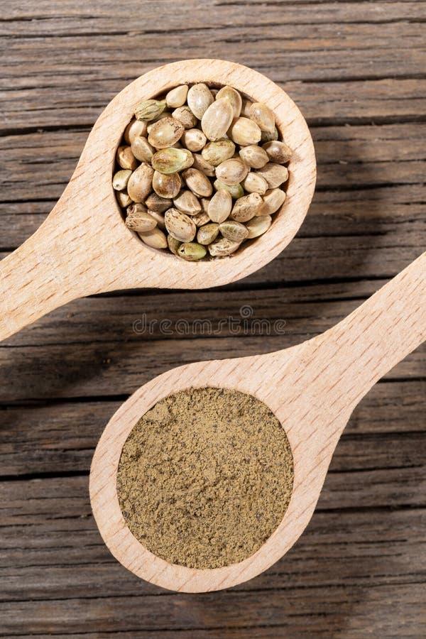 有大麻种子和大麻面粉的两把木匙子在老破裂的木板 免版税库存图片