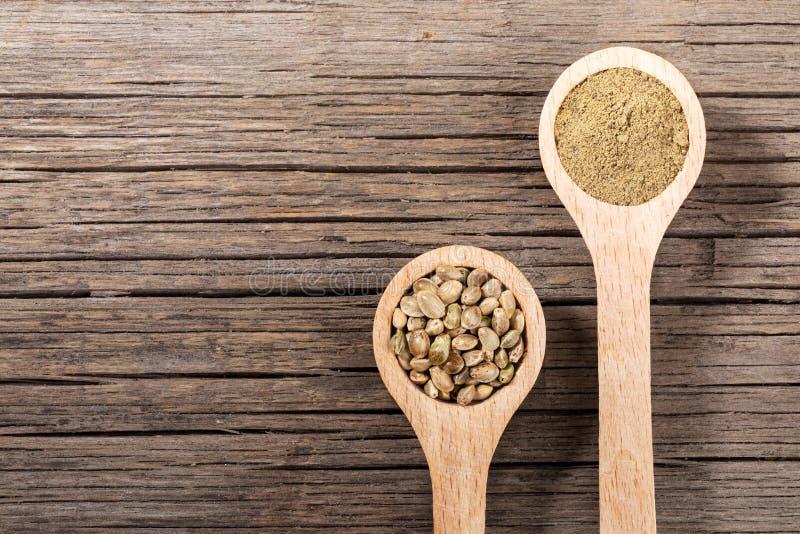 有大麻种子和面粉的两把木匙子在老木板 E 免版税库存图片