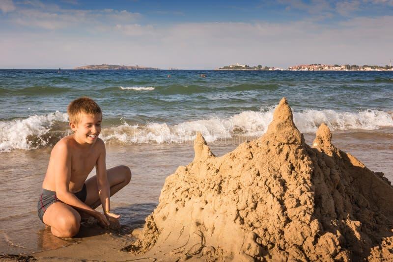 有大黄沙城堡的愉快的少年男孩 库存图片