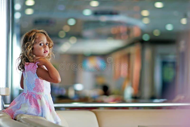 有大黑眼圈的三岁的女孩愉快地充当连接伊古迈尼察到布林迪西的轮渡大厅 库存图片