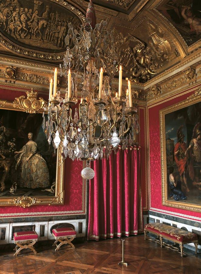 有大绘画和枝形吊灯的在凡尔赛宫,法国红色室 免版税库存图片