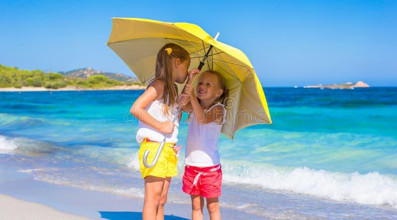 有大黄色伞的小女孩在期间 免版税库存照片