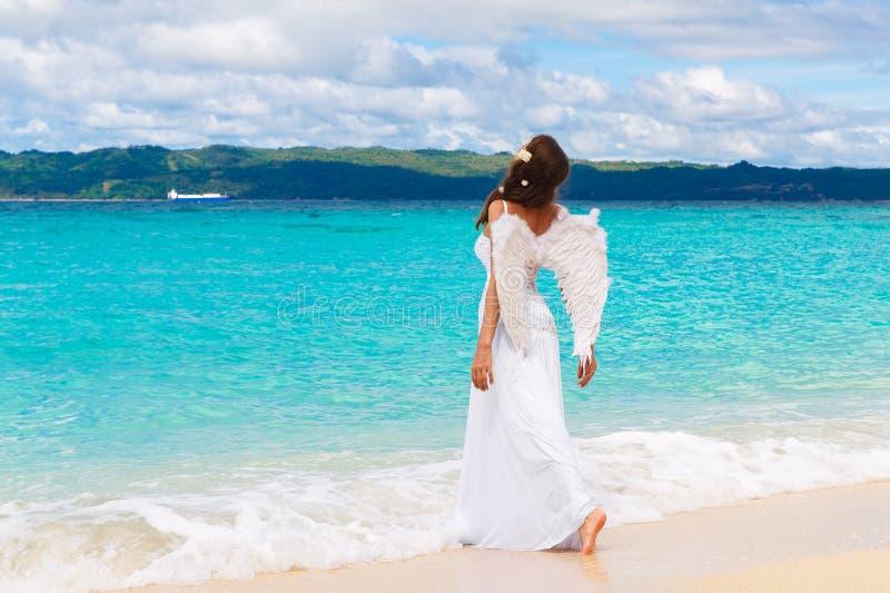 有天使的美丽的年轻新娘在沿海Tropica飞过 库存图片