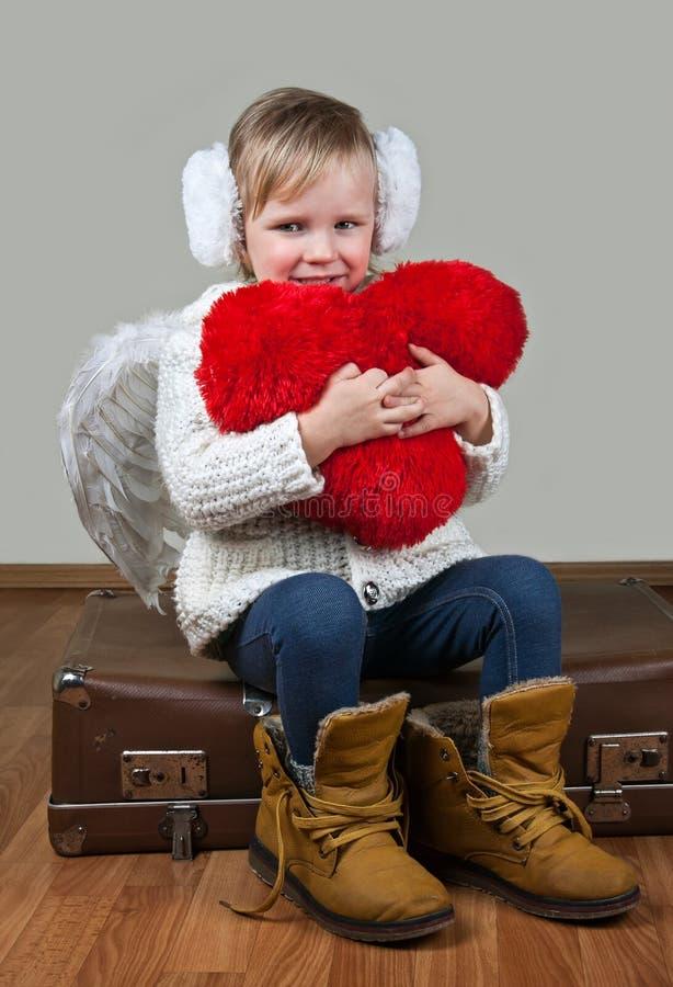有天使翼和心脏的小女孩 库存照片