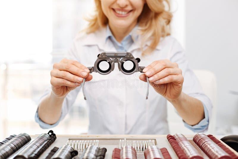 有天才的纯熟眼镜师提供的试验眼镜 库存照片