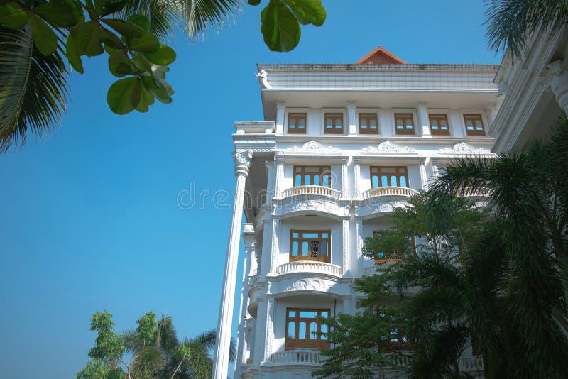 有天空蔚蓝的绿色棕榈围拢的白色印度大厦 库存图片