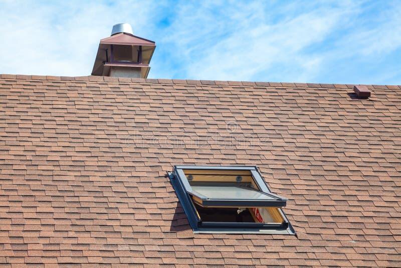 有天窗、沥青屋面木瓦和烟囱的新的屋顶 有有双重斜坡屋顶的房屋的窗口的屋顶 库存照片