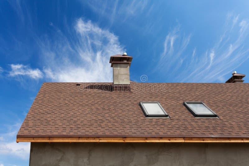 有天窗、沥青屋面木瓦和烟囱的新的屋顶 有有双重斜坡屋顶的房屋的窗口的屋顶 免版税图库摄影