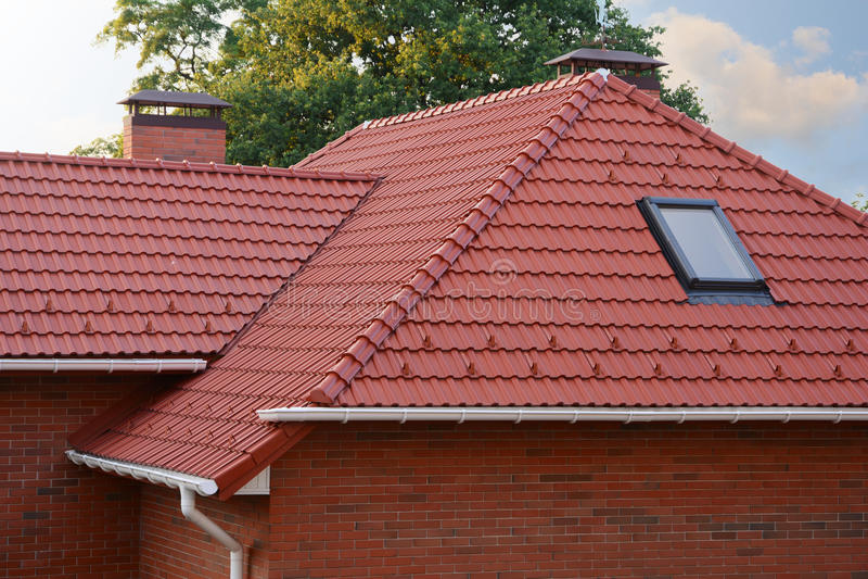 有天窗Windows和雨天沟的新的红色木瓦屋顶 有烟囱的新的砖房子 免版税库存图片