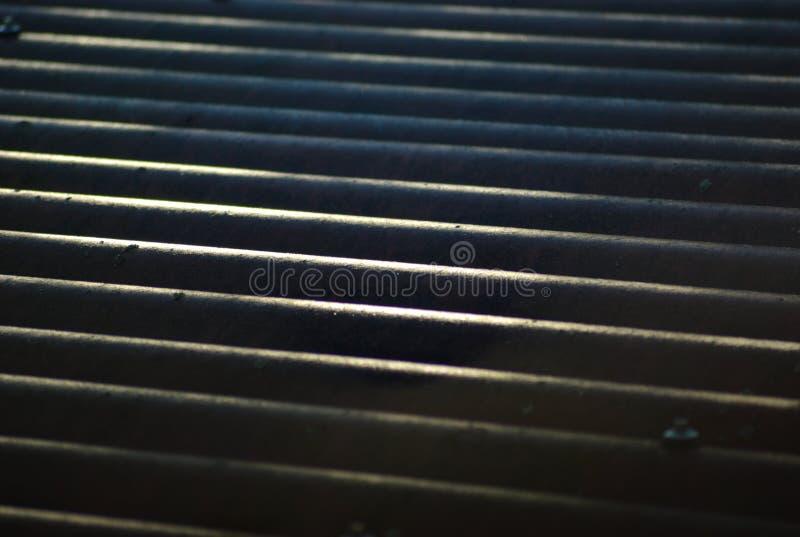 有太阳反射的波纹状的屋顶 免版税库存照片