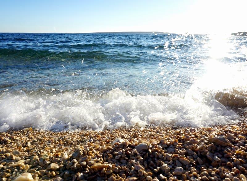 有太阳反射的Pebble海滩在波浪海水和白色泡沫 免版税图库摄影