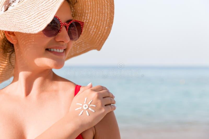有太阳形状的年轻女人在她手工制造在海滩的遮光剂 免版税库存图片