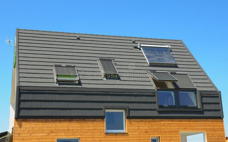 有太阳水加热器的现代房子建筑屋顶 免版税库存照片