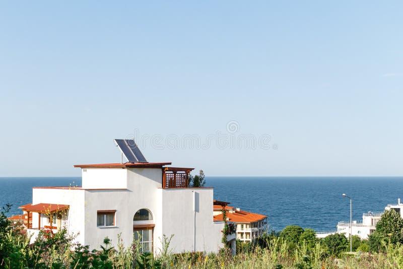 有太阳水加热盘区的白色房子在屋顶和海背景反对天空蔚蓝 Byala,保加利亚 免版税库存照片