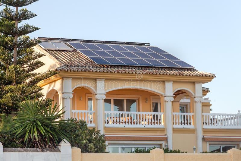 有太阳电池板的别墅房子在屋顶 免版税库存图片