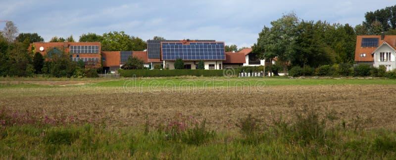 有太阳电池板的村庄议院在屋顶 库存照片