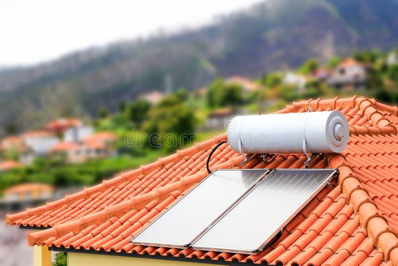 有太阳电池板的水壶在房子屋顶  免版税库存图片
