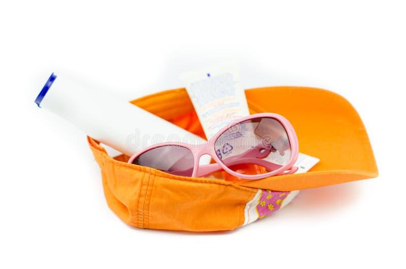 有太阳镜和遮光剂的盖帽 库存图片