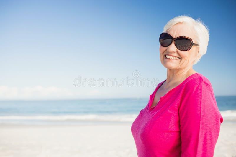 有太阳镜微笑的愉快的资深妇女 图库摄影
