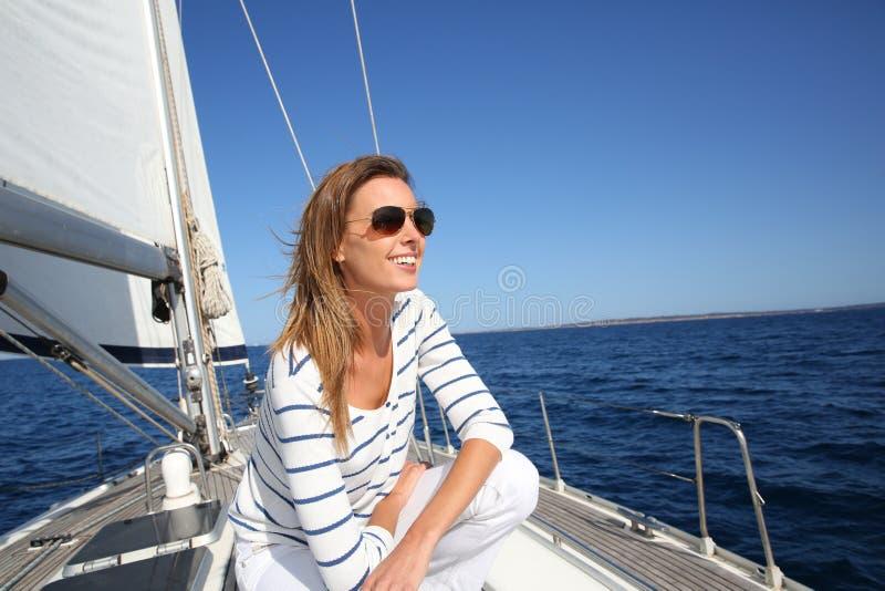 有太阳镜的可爱的现代妇女在巡航 免版税库存图片