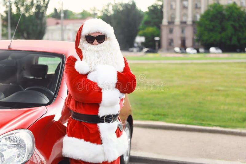 有太阳镜的地道圣诞老人临近汽车 免版税库存照片