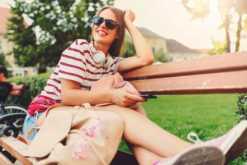 有太阳镜的女孩坐在夏天听的音乐的一条长凳在耳机 免版税库存图片