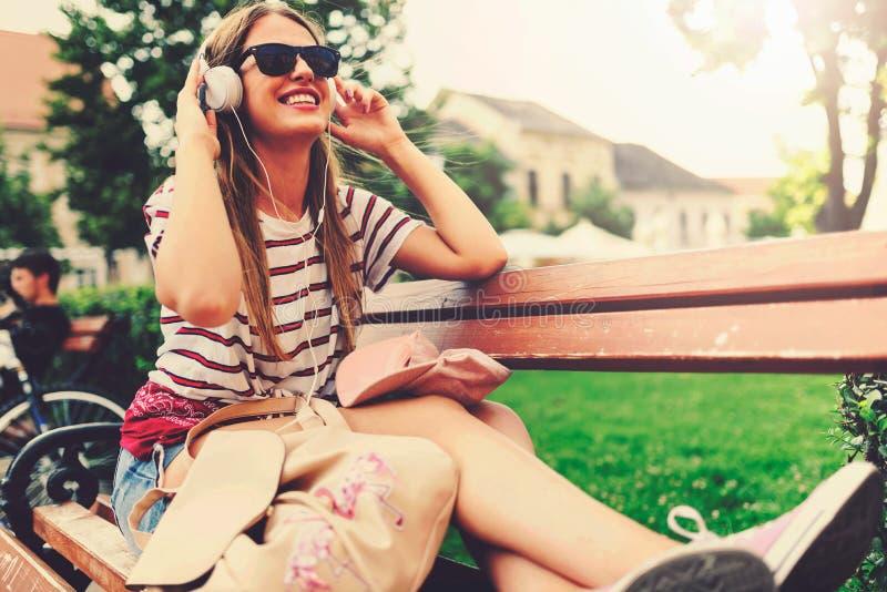 有太阳镜的女孩坐在夏天听的音乐的一条长凳在耳机 免版税库存照片