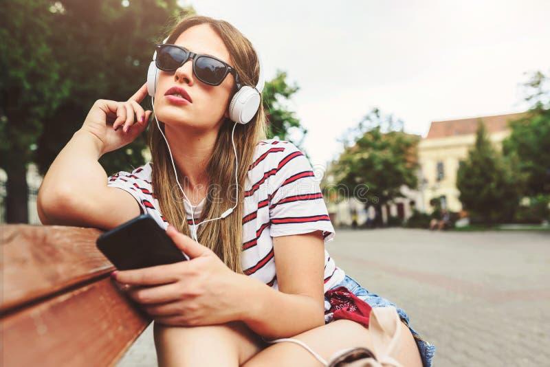 有太阳镜的女孩坐在夏天听的音乐的一条长凳在耳机 免版税图库摄影