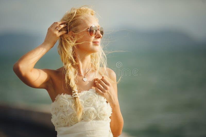 有太阳镜的妇女和在海背景的白色婚礼礼服 图库摄影