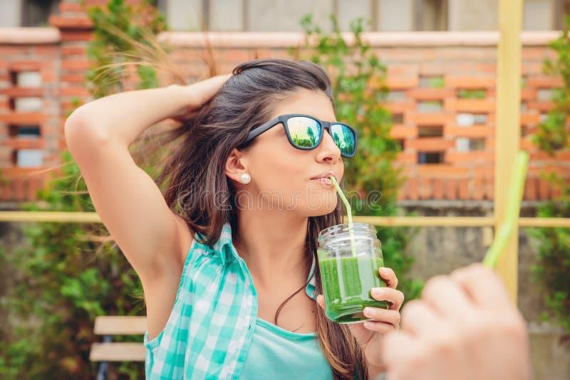 有太阳镜的妇女喝绿色菜的 免版税图库摄影