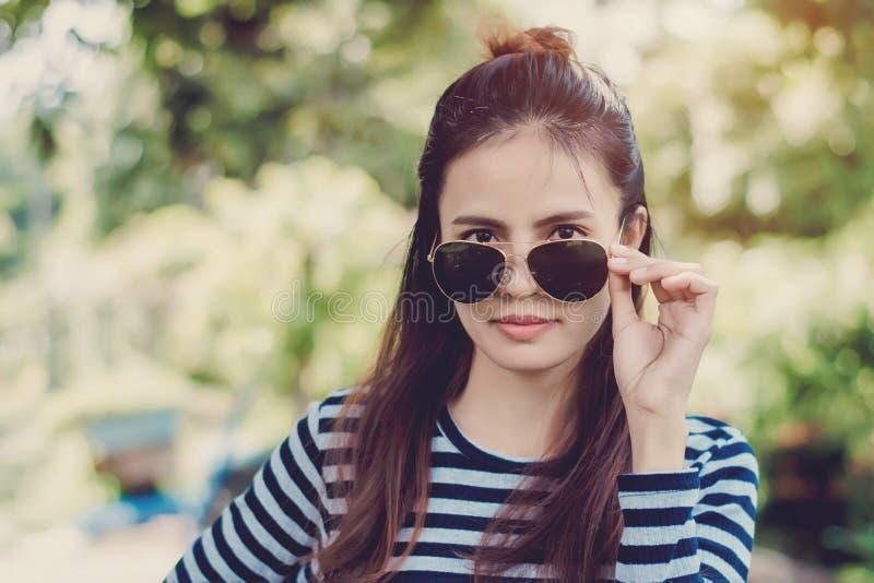 有太阳镜的妇女行家塑造样式生活方式概念,穿一件黑白镶边T恤杉 免版税库存图片