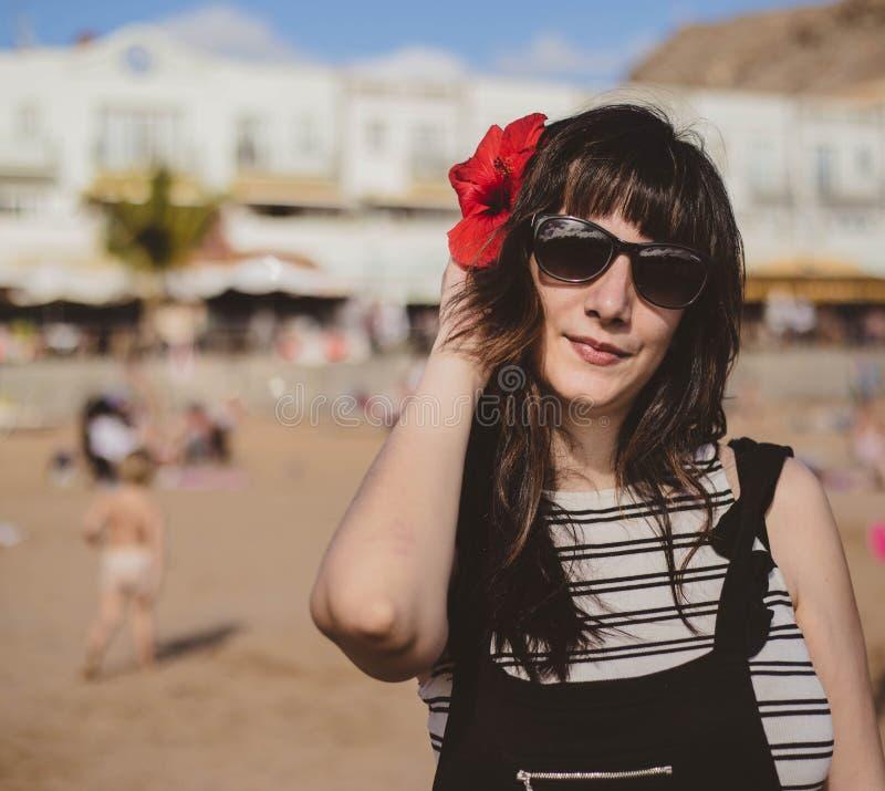 有太阳镜的年轻深色的妇女在与一朵红色花的海滩在她的头发 免版税库存照片