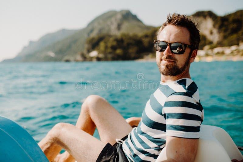 有太阳镜的成熟人坐小船在度假夏天休假 库存图片