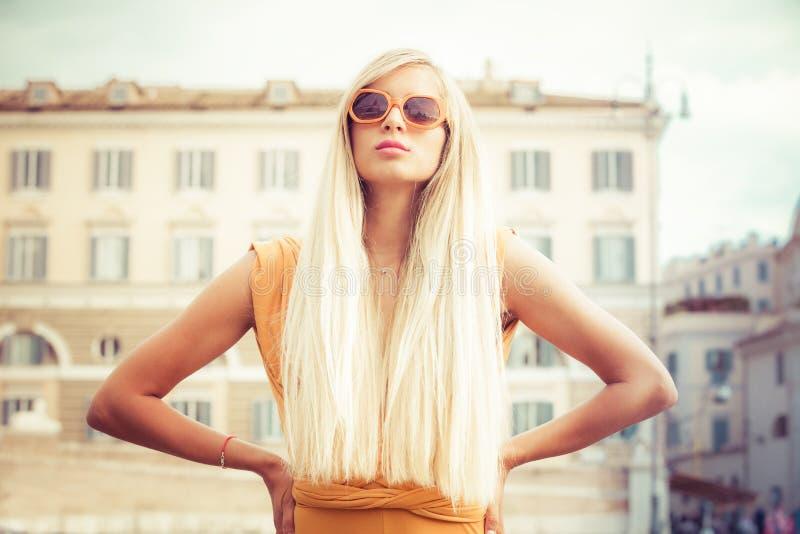有太阳镜的时髦的长的金发少妇在城市 免版税图库摄影