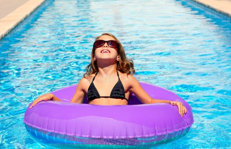 有太阳镜的比基尼泳装女孩和可膨胀的池敲响 免版税库存图片