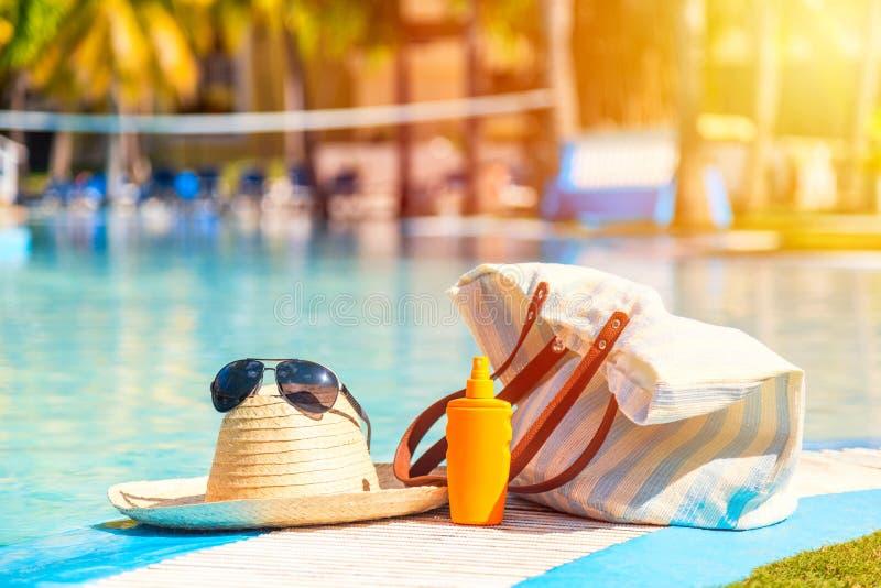 有太阳镜的草帽在遮光剂化妆水反对蓝色清楚的游泳场表面的瓶和海滩袋子附近  夏天 免版税图库摄影