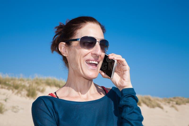 有太阳镜的蓝色毛线衣妇女谈话在机动性 免版税库存照片
