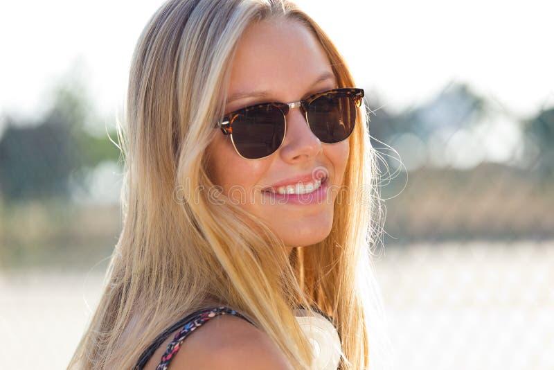 有太阳镜的年轻可爱的妇女在一个夏日 免版税库存照片