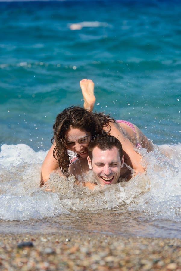有夫妇的乐趣飞溅水波 免版税库存照片