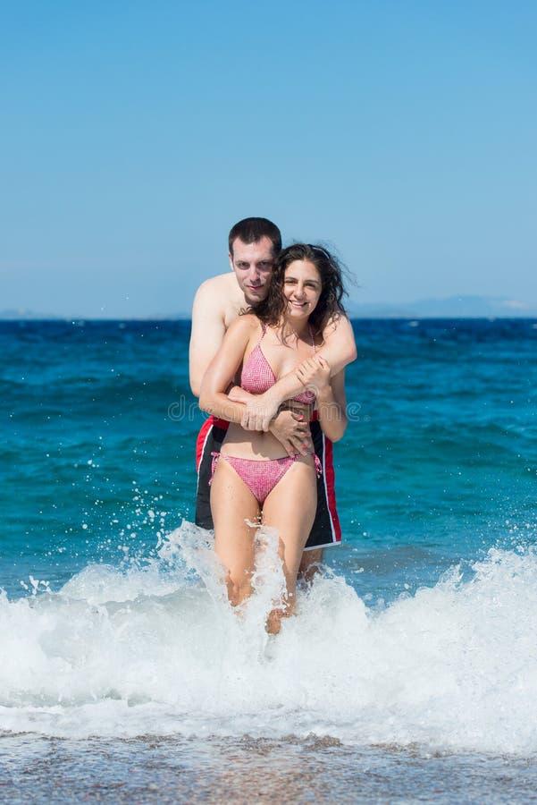 有夫妇的乐趣飞溅水波 免版税图库摄影