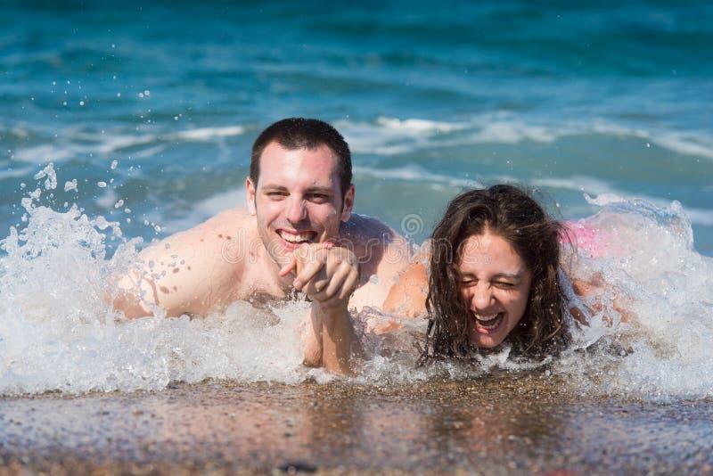 有夫妇的乐趣飞溅水波 免版税库存图片